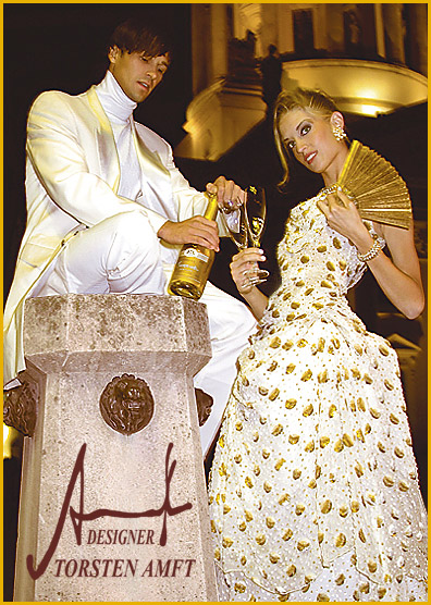 The model Vera Gafron in a champagne colored chiffon gala robe with gold Lamè patterns and the man, Marcel Haas in a gala smoking with cashmere sweater manufactured by German fashion designer Torsten Amft from Berlin.